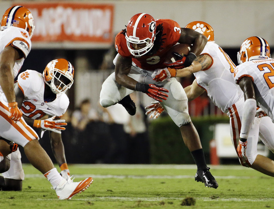 Photo - Georgia's Todd Gurley, center, runs the ball against the Clemson defense in the second half of an NCAA college football game, Saturday, Aug. 30, 2014, in Athens, Ga. Gurley ran for 198 yards and three touchdowns, returned a kickoff 100 yards for another score, and No. 12 Georgia gained some early style points in the national race with a 45-21 victory over No. 16 Clemson on Saturday night. (AP Photo/David Goldman)