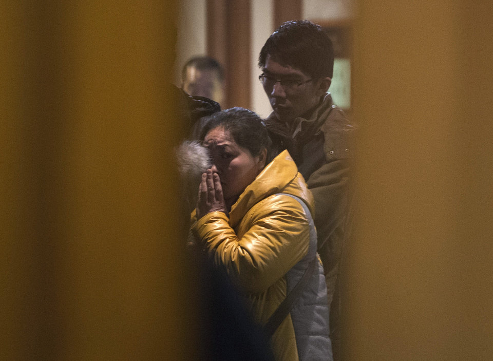 Photo - A Chinese relative of passengers aboard a missing Malaysia Airlines plane looks out from a hotel room for relatives or friends of passengers aboard the missing airplane in Beijing, China Monday, March 10, 2014. Vietnamese aircraft spotted what they suspected was one of the doors of the missing Boeing 777 on Sunday, while questions emerged about how two passengers managed to board the ill-fated aircraft using stolen passports. (AP Photo/Andy Wong)