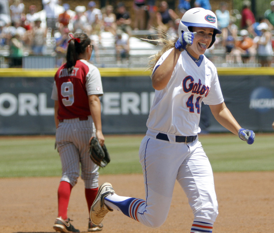 Photo - Florida's Brittany Schutte (44) celebrates in front Alabama's Courtney Conley (9) during the Women's College World Series game between Florida and Alabama at the ASA Hall of Fame Stadium in Oklahoma City, Sunday, June 5, 2011. Photo by Sarah Phipps, The Oklahoman