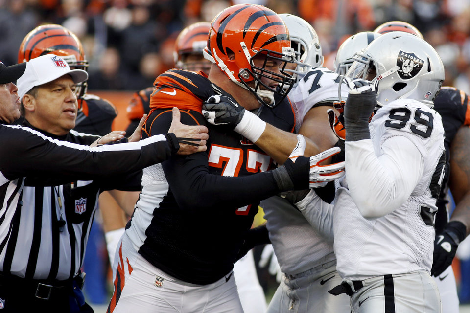 Photo -   Cincinnati Bengals tackle Andrew Whitworth (77) fights with Oakland Raiders defensive end Lamarr Houston (99) in the second half of an NFL football game, Sunday, Nov. 25, 2012, in Cincinnati. Both players were ejected from the game. The Bengals won 34-10. (AP Photo/David Kohl)