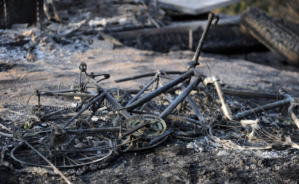 Photo - The remains of a mountain bike lays in the ashes outside a house along Holmes Road Thursday, June 13, 2013, during the third day of the Black Forest Fire north of Colorado Springs, Colo.(AP Photo/The Gazette, Christian Murdock) MAGS OUT