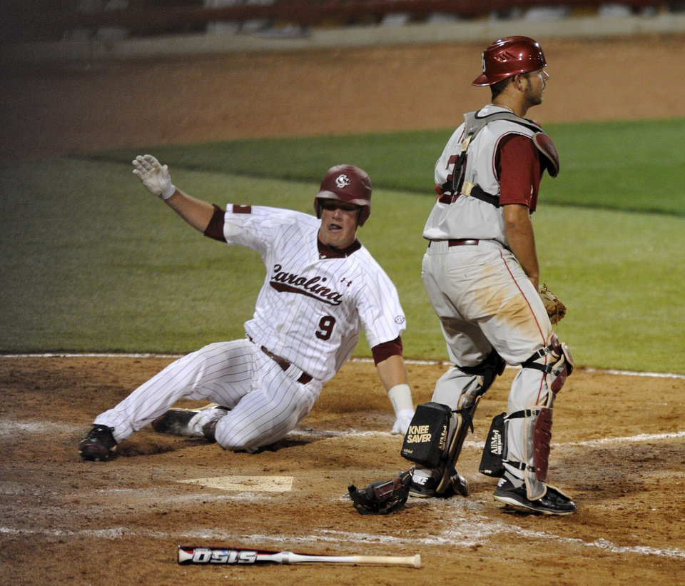 Photo - South Carolina's Joey Pankake (9) slides safely into home plate as Oklahoma's Tanner Toel waits for the throw in the seventh inning of an NCAA college super regional baseball tournament game in Columbia, S.C., Saturday, June 9, 2012. South Carolina won 7-0. (AP Photo/Mary Ann Chastain) ORG XMIT: SCMC111