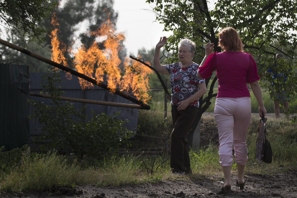 Photo - Local residents talk to each other as they look at flame from a damaged gas pipe after an impact of a mortar bomb, during fighting between Ukrainian government troops and pro-Russian militants, outside Slovyansk, eastern Ukraine, early Monday, May 19, 2014. Lawmakers and officials from eastern Ukraine on Saturday poured criticism on the fledging central government, accusing it of ignoring legitimate grievances of the regions which have been overrun by pro-Russia militia fighting for independence. (AP Photo/Alexander Zemlianichenko)