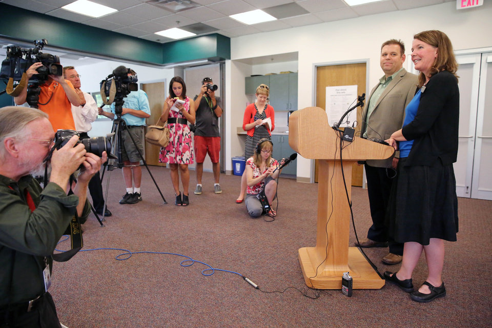 Photo - Boulder County Clerk Hillary Hall, far right, stands with Deputy County Attorney David Hughes, taking questions during a news conference at the offices of the Boulder County Clerk and Recorder, in Boulder, Colo., Thursday, July 10, 2014. District Court Judge Andrew Hartman ruled Thursday July 10 that gay couples can keep getting married in Colorado. The decision by Hartman said that Boulder County Clerk Hall can ignore a federal stay on a ruling from the 10th U.S. Circuit Court of Appeals in Denver, which found states cannot set gender requirements for marriage. (AP Photo/Brennan Linsley)