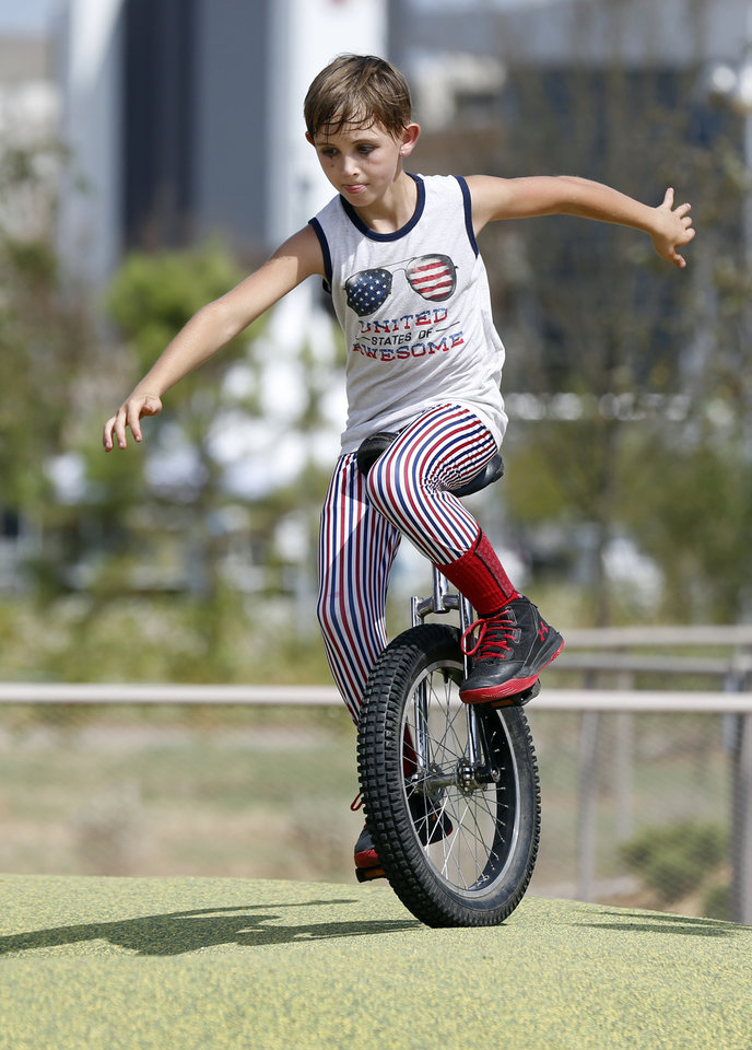 Photo - Bryce Rainwater, 11, rides a unicycle in the children's playground during the grand opening weekend of Scissortail Park in Oklahoma City, Saturday, Sept. 28, 2019. [Nate Billings/The Oklahoman]