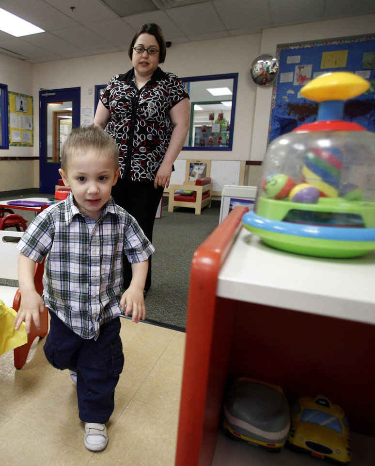 Photo -   In this April 4, 2012, photo, Kelly Andrus follows her son Bradley as he runs through a classroom at Children's Choice Learning Centers Inc., where Bradley attends in Lewisville, Texas. Bradley, who turns three in a couple of weeks, was diagnosed a year ago with mild autism. For the first time in nearly two decades, experts want to rewrite the definition of autism. Some parents fear that if it's narrowed and their kids lose the label, they may also lose out on special therapist. (AP Photo/Tony Gutierrez)