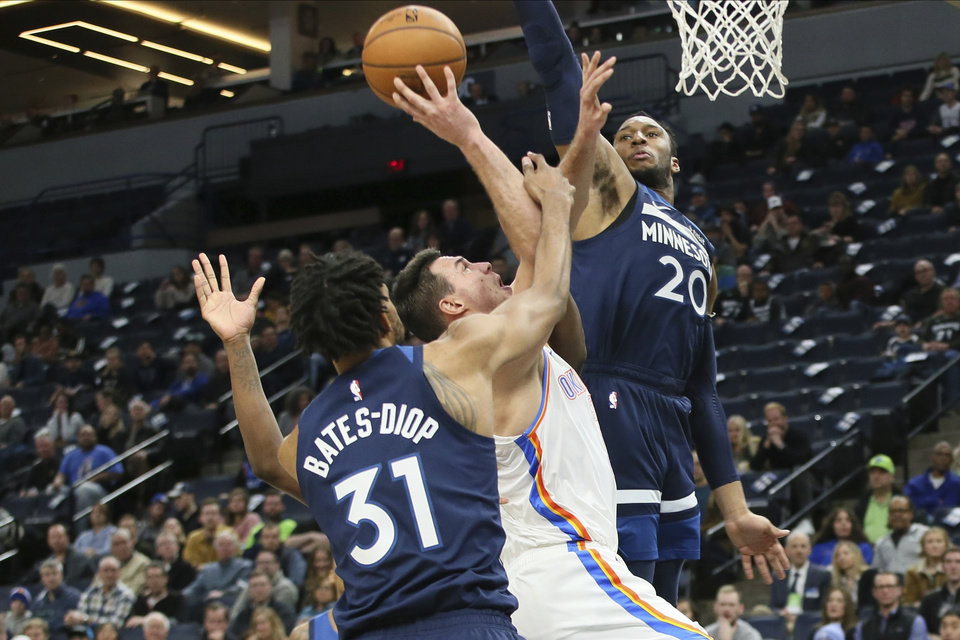 Photo - Oklahoma City Thunder's Danilo Gallinari, center, of Italy, shoots as he is double-teamed by Minnesota Timberwolves' Keita Bates-Diop, left, and Josh Okogie in the second half of an NBA basketball game Monday, Jan. 13, 2020, in Minneapolis. Gallinari led the Thunder with 30 points in their 117-104 win. (AP Photo/Jim Mone)
