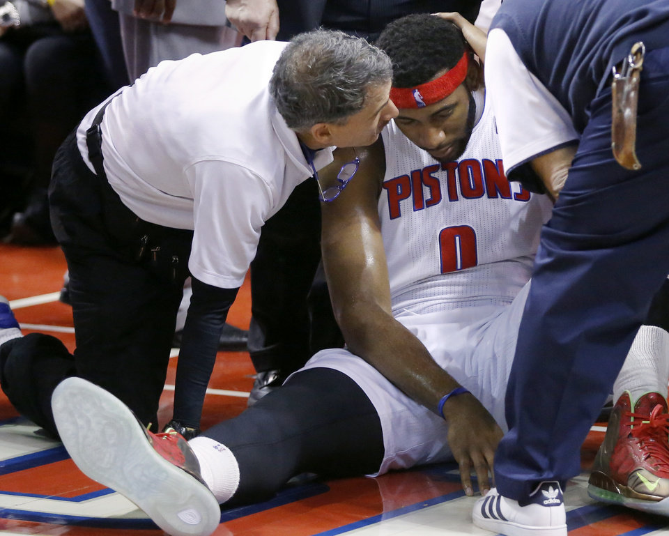 Photo - Detroit Pistons center Andre Drummond (0) is looked at by training staff after getting hit on the head during the first half of an NBA basketball game against the Indiana Pacers Saturday, March 15, 2014, in Detroit. Drummond was helped off the court and did not return. (AP Photo/Duane Burleson)