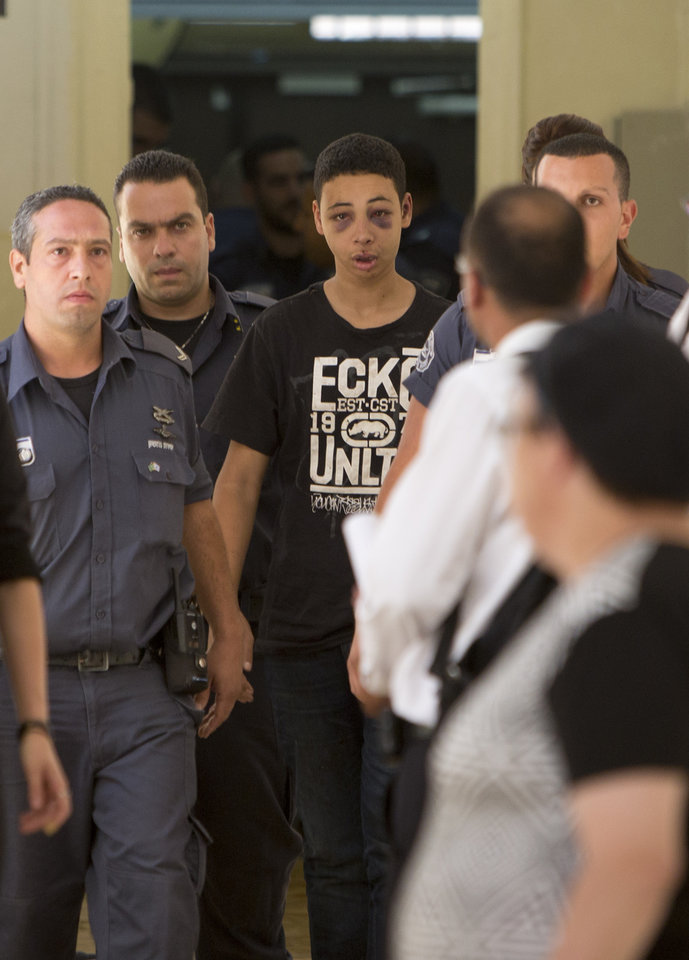 Photo - Tariq Abu Khdeir, 15, a Palestinian-American who relatives say was beaten and arrested by Israeli police during clashes sparked by the killing Thursday of his cousin Mohammed Abu Khdeir, is escorted by Israeli prison guards during an appearance at Jerusalem magistrate's court Sunday, July 6, 2014. Israeli  police said Tariq Abu Khdeir resisted arrest, attacked officers and was carrying a slingshot for lobbing stones when he was arrested. He has been sentenced to nine days of house arrest. The U.S. State Department said it was