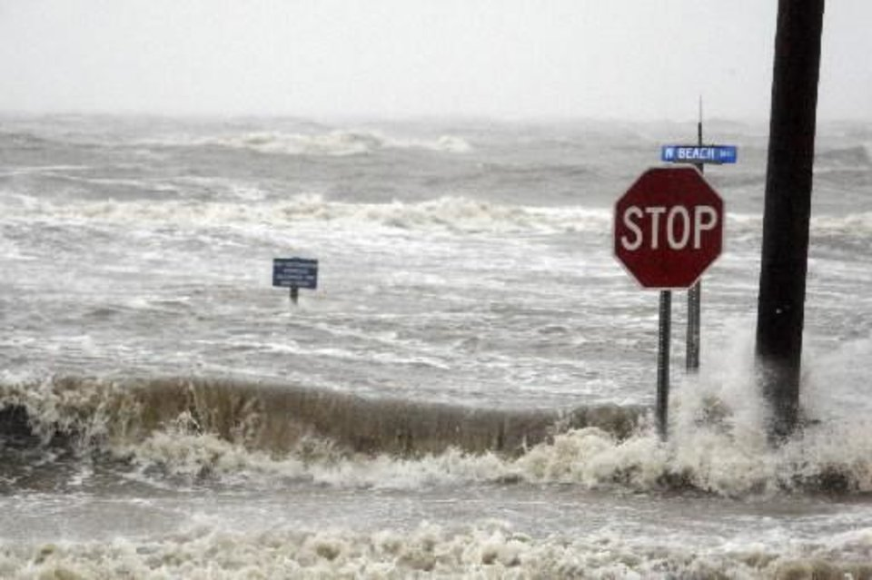 Photo - Isaac's winds and storm surge overcomes the seawall and floods Beach Boulevard in Waveland, Miss., Wednesday, Aug. 29, 2012, the seventh anniversary of Hurricane Katrina hitting the Gulf Coast. (AP Photo/Rogelio V. Solis)
