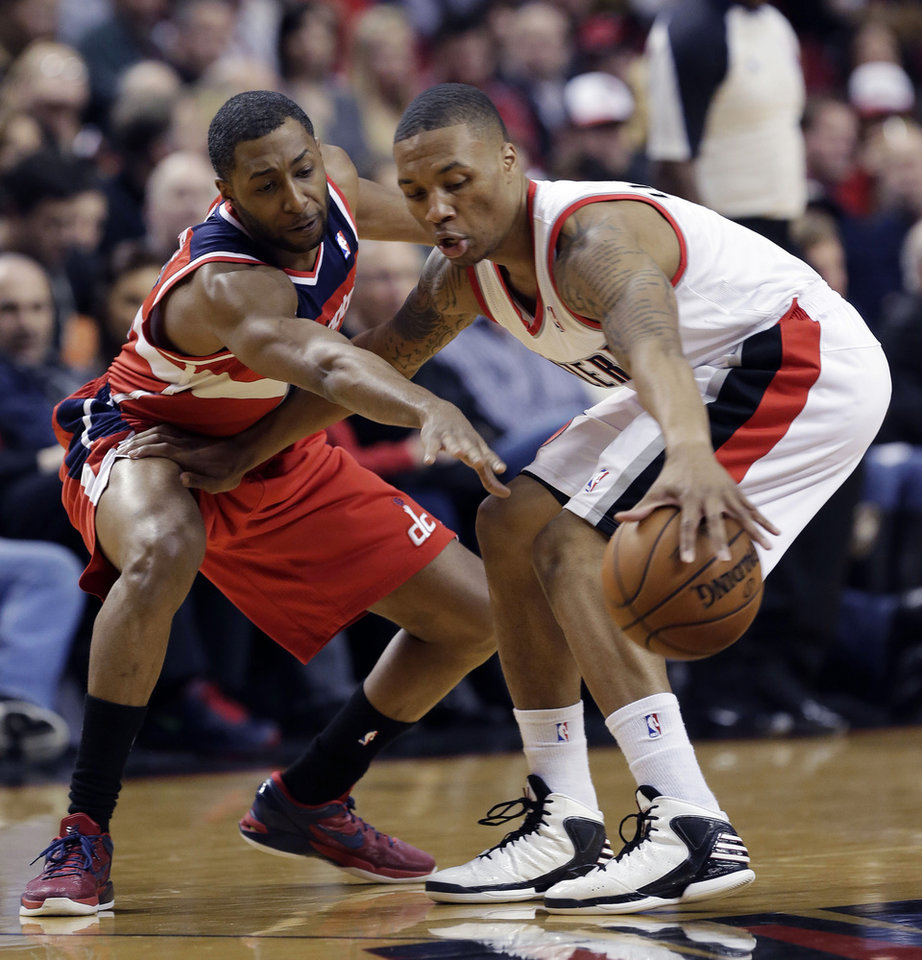 Washington Wizards guard A.J. Price, left, plays tight defense on Portland Trail Blazers guard Damian Lillard during the first quarter of an NBA basketball game in Portland, Ore., Monday, Jan. 21, 2013. (AP Photo/Don Ryan)