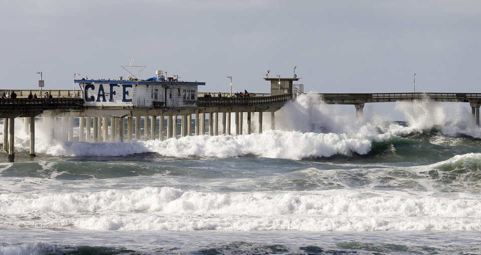 Photo - Large waves break under the Ocean Beach pier Friday, Dec. 11, 2015, in San Diego. Large waves lashed much of the Southern California coastline Friday, prompting the National Weather Service to issue a high surf warning through the weekend. (AP Photo/Gregory Bull)