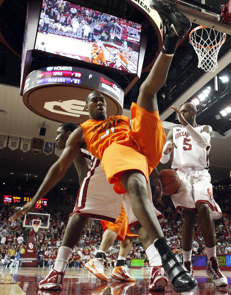 Photo - OSU's Matt Pilgrim (31) falls to the floor while fighting for a rebound with the OU offense during the second half of the college bedlam basketball game between The University of Oklahoma Sooners (OU) and Oklahoma State University University Cowboys (OSU) at the Lloyd Noble Center on Monday, Jan. 11, 2010, in Norman, Okla.