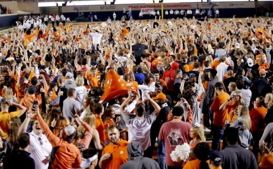 Photo -  OSU fans celebrate after rushing the field following a 38-35 victory over Texas last October. [Sarah Phipps/The Oklahoman]