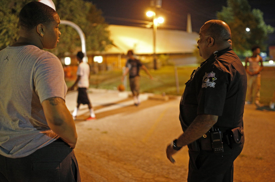 Photo -  Cameron Smiley, 16, talks with an Oklahoma County Sheriff's deputy during midnight basketball at Christ Temple Community Church in Oklahoma City on July 25. Photo by Sarah Phipps, The Oklahoman   SARAH PHIPPS -  SARAH PHIPPS