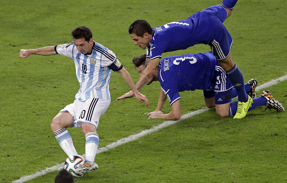 Photo - Argentina's Lionel Messi, left, scores his side's second goal during the group F World Cup soccer match between Argentina and Bosnia at the Maracana Stadium in Rio de Janeiro, Brazil, Sunday, June 15, 2014.  (AP Photo/Sergei Grits)