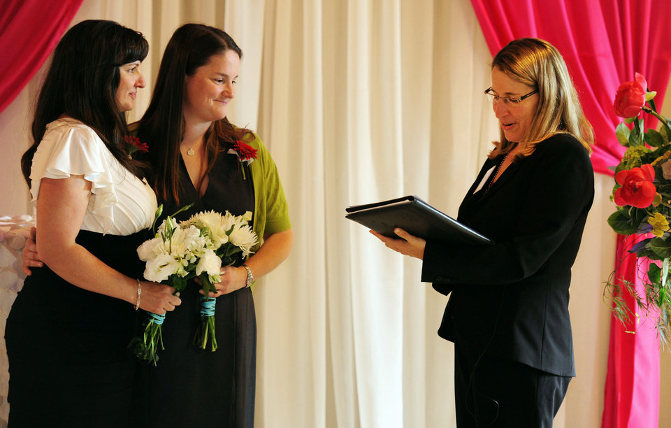 Photo - Julia Fraser, left, and Jessica Rohrbacher  get married by Holly Pruett at the Melody Ballroom in Portland, Ore. on Monday, May. 19, 2014. Federal Judge Michael McShane released an opinion Monday on Oregon's Marriage Equality lawsuit that grants gay and lesbian couples the freedom to marry in Oregon.  (AP Photo/Steve Dykes)