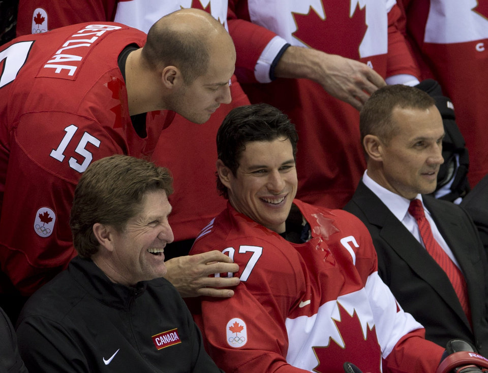 Photo - Team Canada's Ryan Getzlaf looks over the shoulder of Sidney Crosby, head coach Mike Babcock, left,  and General Manager Steve Yzerman during the team photo at the start of practice at the Sochi Winter Olympics, Tuesday Feb. 11, 2014, in Sochi, Russia. (AP Photo/The Canadian Press, Adrian Wyld)