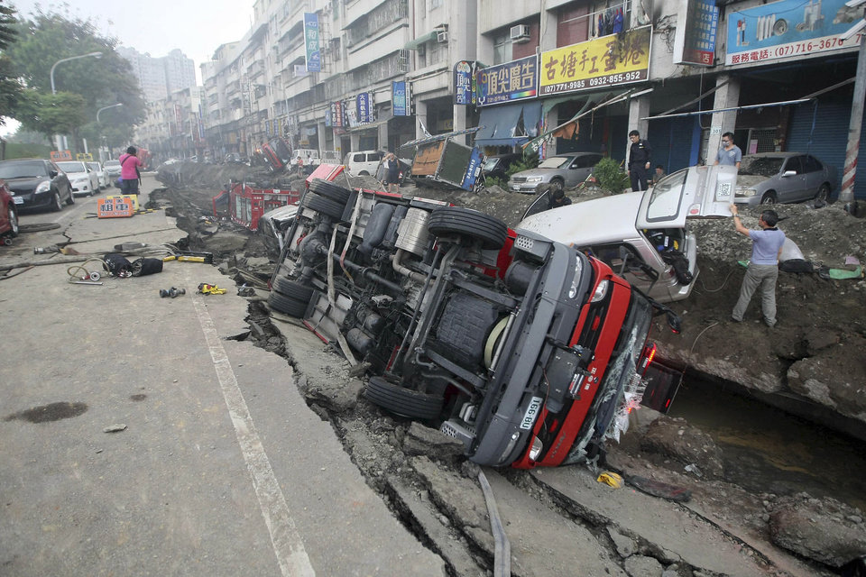 Photo - People inspect vehicles tipped over following multiple explosions from an underground gas leak in Kaohsiung, Taiwan, early Friday, Aug. 1, 2014. A massive gas leakage early Friday caused five explosions that killed scores of people and injured over 200 in the southern Taiwan port city of Kaohsiung. (AP Photo) TAIWAN OUT
