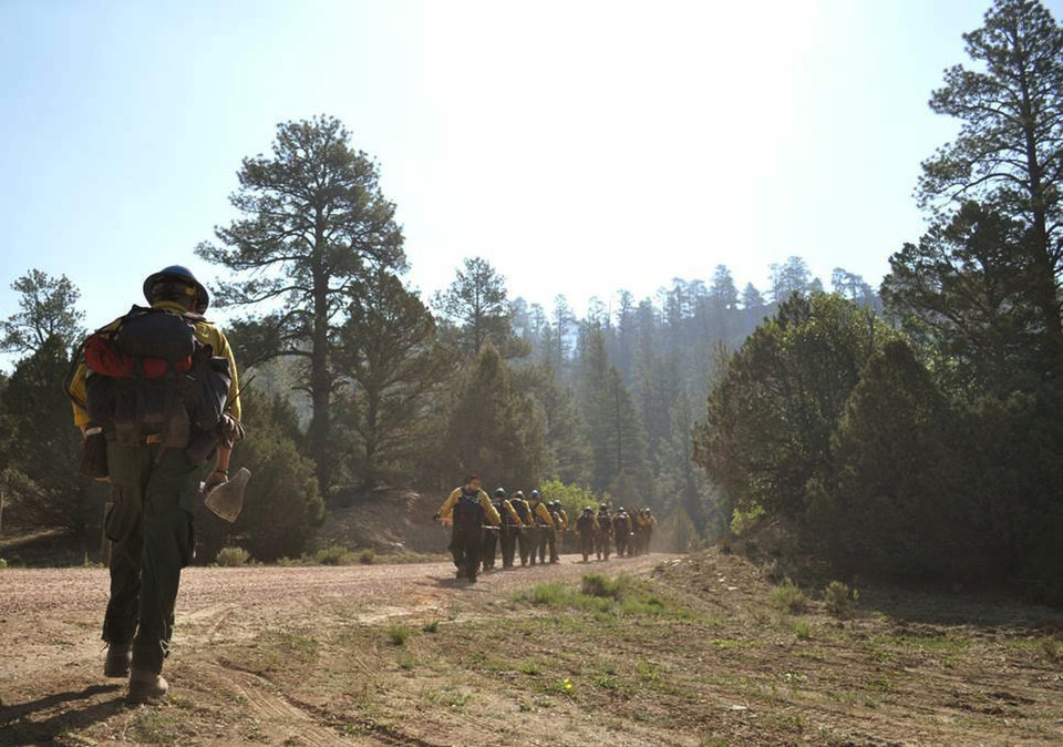 Photo - In this Sunday, June 15, 2014, photo the Navajo Hotshots make their way to the fire in the Chuska Mountains near Asaayi Lake, which is east of Navajo Pine, N.M. Residents of two Native American communities near the New Mexico-Arizona border were forced to leave their homes Monday, June 16, 2014, as strong winds fanned the flames of a wildfire burning in the Chuska Mountains. The blaze ballooned to more than 17 square miles, forcing Navajo Nation police to issue an evacuation order for parts of Naschitti and nearby Sheep Springs. (AP Photo/Navajo Times, Ravonelle Yazzie)