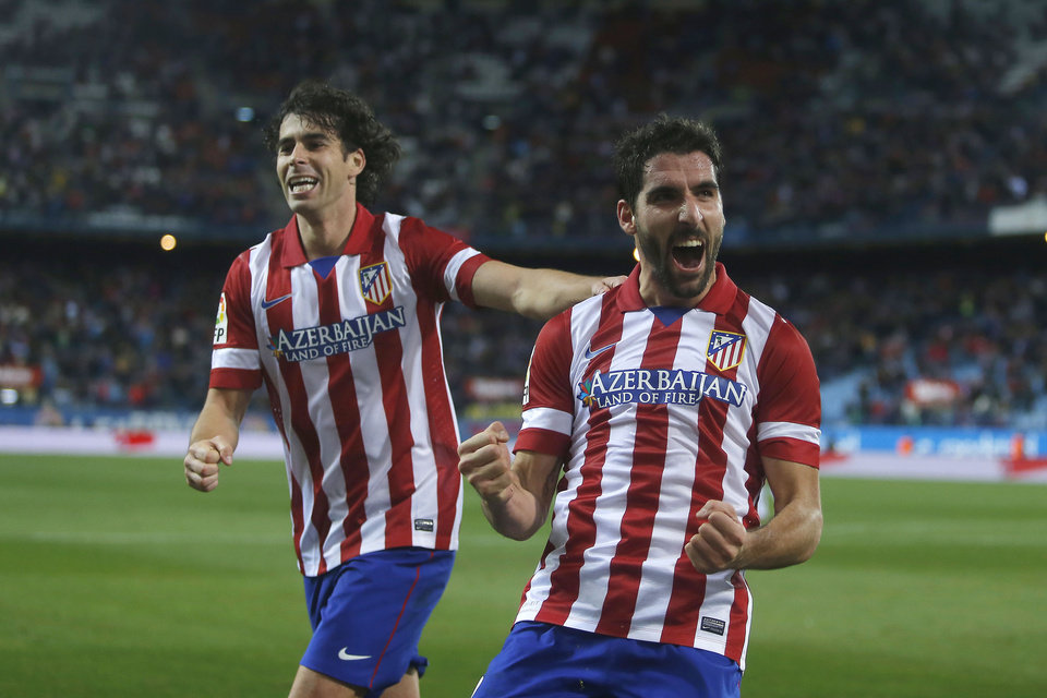 Photo - Atletico's Raul Garcia, centre, celebrates his goal with Tiago during a Spanish Copa del Rey soccer match between Atletico de Madrid and Valencia at the Vicente Calderon stadium in Madrid, Spain, Tuesday, Jan. 14, 2014. (AP Photo/Andres Kudacki)