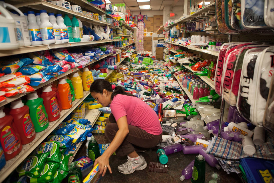 Photo - Nina Quidit cleans up the Dollar Plus and Party Supplies Store in American Canyon Calif., after an earthquake on Sunday, Aug. 24, 2014. Quidit and her husband were woken up in the early morning hours by the store's alarm company and immediately drove in to begin cleaning up. (AP Photo/Alex Washburn)