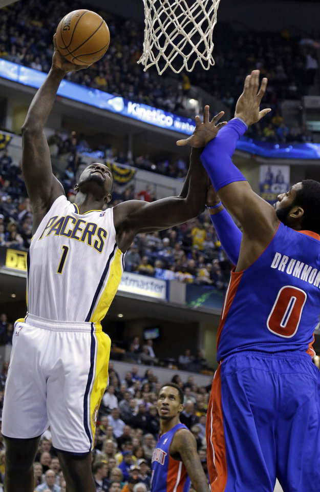 Photo - Indiana Pacers guard Lance Stephenson, left, shoots over Detroit Pistons center Andre Drummond in the second half of an NBA basketball game in Indianapolis, Monday, Dec. 16, 2013. The Pistons defeated the Pacers 101-96. (AP Photo/Michael Conroy)