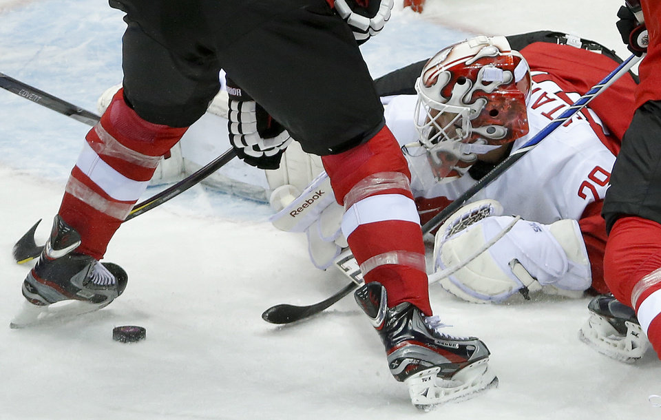 Photo - Austria goaltender Bernhard Starkbaum drops to the ice to smother a rebound against Finland in the first period of a men's ice hockey game at the 2014 Winter Olympics, Thursday, Feb. 13, 2014, in Sochi, Russia. (AP Photo/Mark Humphrey)