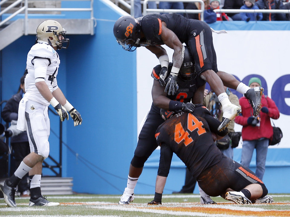 Photo - Oklahoma State celebrates a touchdown during the Heart of Dallas Bowl football game between the Oklahoma State University (OSU) and Purdue University at the Cotton Bowl in Dallas,  Tuesday,Jan. 1, 2013. Photo by Sarah Phipps, The Oklahoman