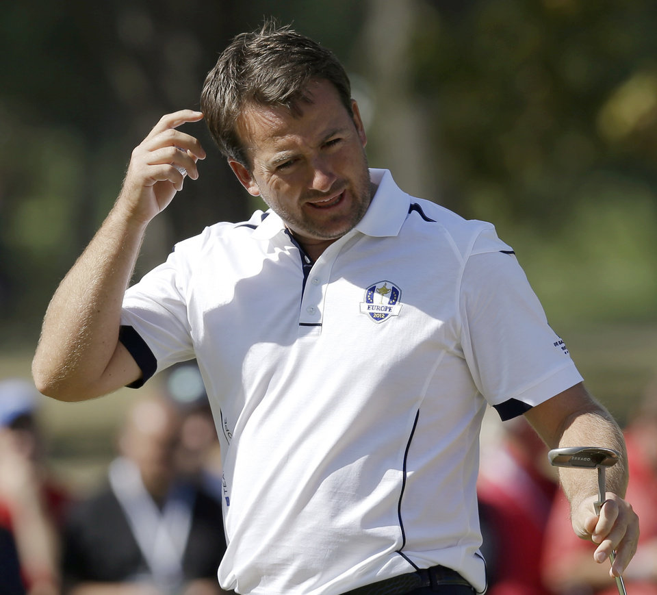 Europe's Graeme McDowell reacts after missing a putt on the third hole during a singles match at the Ryder Cup PGA golf tournament Sunday, Sept. 30, 2012, at the Medinah Country Club in Medinah, Ill. (AP Photo/David J. Phillip)  ORG XMIT: PGA131