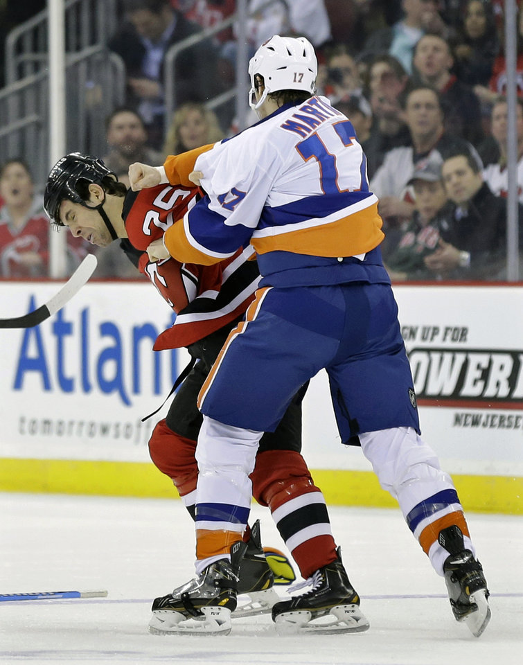 Photo - New York Islanders' Matt Martin (17) and New Jersey Devils Tom Kostopoulos (25) fight during the first period of an NHL hockey game Monday, April 1, 2013, in Newark, N.J. (AP Photo/Mel Evans)