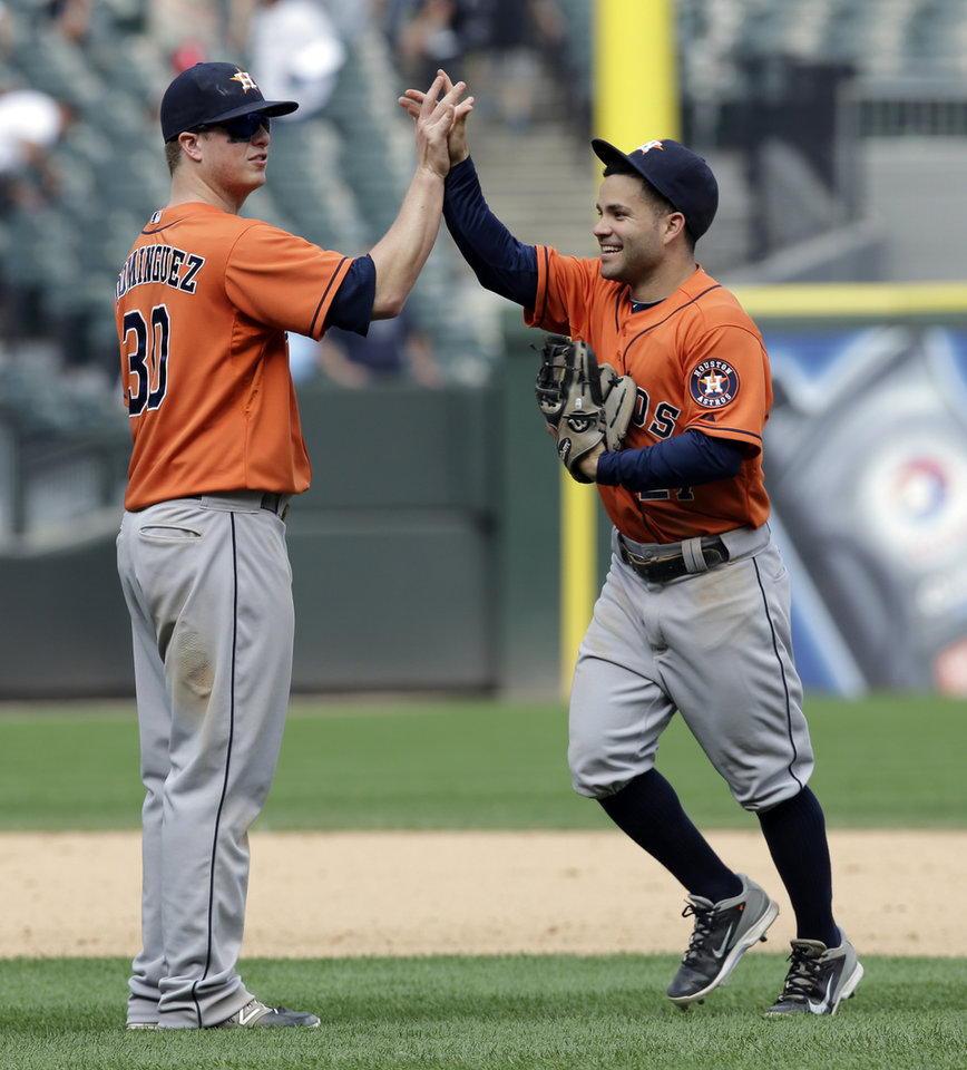 Photo - Houston Astros' Matt Dominguez, left, celebrates with Jose Altuve after the Astros defeated the Chicago White Sox 11-7 in a baseball game in Chicago on Sunday, July 20, 2014. (AP Photo/Nam Y. Huh)