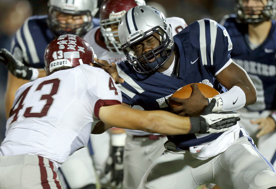 Photo - Edmond North's Michael Farmer fights off Grant Carro during a high school football playoff game at Wantland Stadium in Edmond, Okla., Thursday, Nov. 8, 2012. Photo by Bryan Terry, The Oklahoman