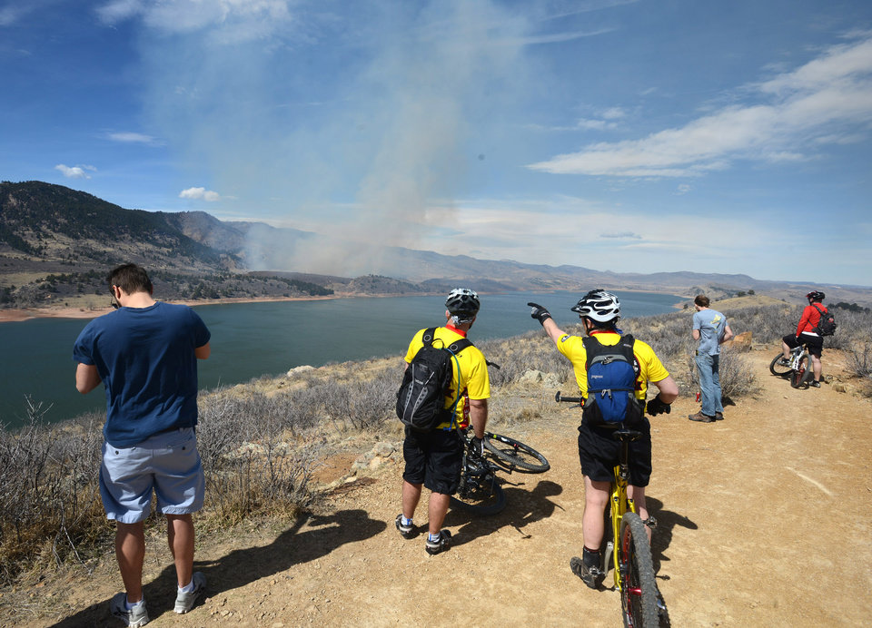 Photo - Onlookers stop to watch the fire on the east side of Horsetooth Reservior west of Fort Collins, Colo., on Friday, March 15, 2013. The 40-acre wildfire burning in gusty winds and warm weather was threatening homes west of Fort Collins on Friday and prompted about 50 people to leave the area. (AP Photo/The Coloradoan, V. Richard Haro)