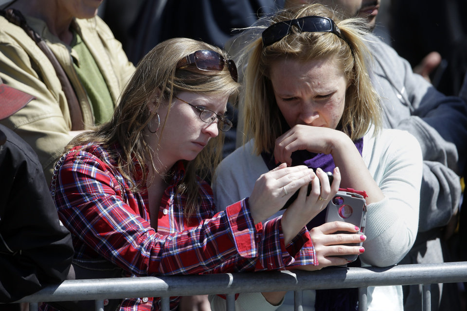 Nursing students Katie Robinson, left, and Megan Beach listen to a broadcast on their phones from outside an interfaith service attended by President Barack Obama at the Cathedral of the Holy Cross, held in the wake of Monday's Boston Marathon explosions, which killed at least three and injured more than 140, Thursday, April 18, 2013, in Boston. (AP Photo/Matt Rourke)