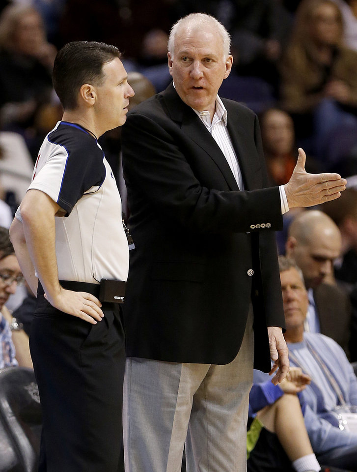 San Antonio Spurs coach Gregg Popovich talks with referee Pat Fraher during the first half of an NBA basketball game against the Phoenix Suns, Sunday, Feb. 24, 2013, in Phoenix. (AP Photo/Matt York)