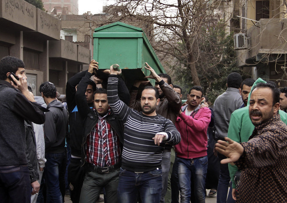 Photo - Egyptians carry the coffin of a man killed during Saturday's clashes between protesters and security forces near the Zeinhom morgue in Cairo, Egypt, Sunday, Jan. 26, 2014. Egyptian officials said Sunday that the death toll from clashes between security forces and protesters on the third anniversary of the country's 2011 uprising has risen to 49. (AP Photo/Aly Hazzaa, El Shorouk) EGYPT OUT