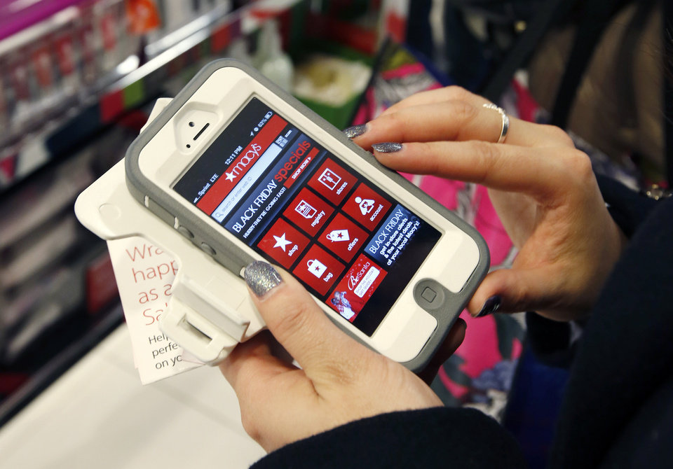 Photo - FILE - In this Friday, Nov. 23, 2012, file photo, Tashalee Rodriguez, of Boston, uses her smartphone while shopping at Macy's in downtown Boston. Facebook isn't just for goofy pictures and silly chatter. Whether shoppers know it or not, their actions online help dictate what's in stores during this holiday season. (AP Photo/Michael Dwyer, File)