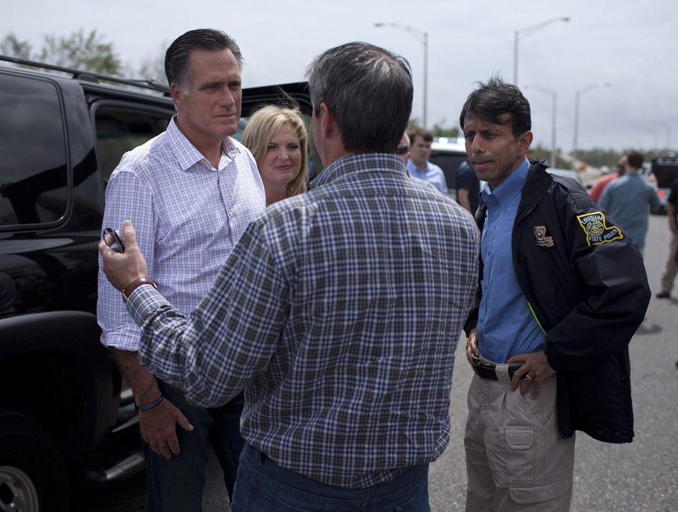 Photo -   Republican presidential candidate, former Massachusetts Gov. Mitt Romney, his wife Ann, center, and Gov. Bobby Jindal, R-La., right, talk with Sen. David Vitter, R-La., back to camera, during a tour of flooding caused by hurricane Isaac, Friday, Aug. 31, 2012, in Jean Lafitte, La. (AP Photo/Evan Vucci)