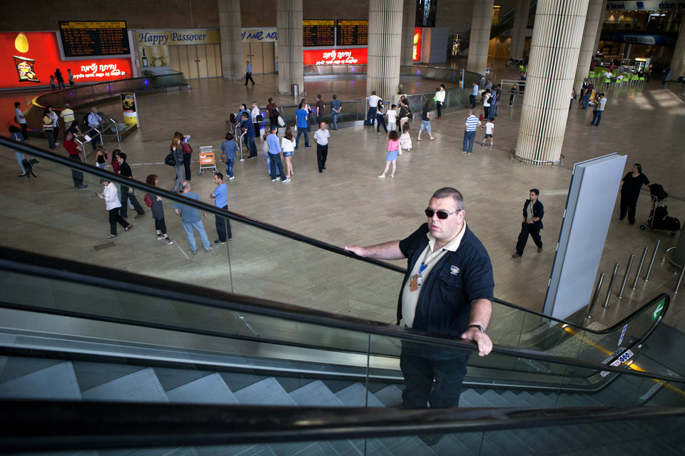 An Israeli Security guard rides an escalator at the arrival terminal in Ben Gurion Air Port in Tel Aviv, Saturday, April 14, 2012. A coordinator of a mass fly-in of pro-Palestinian activists into Israel's main airport say airlines have canceled flights for at least 100 people. (AP Photo/Dan Balilty)