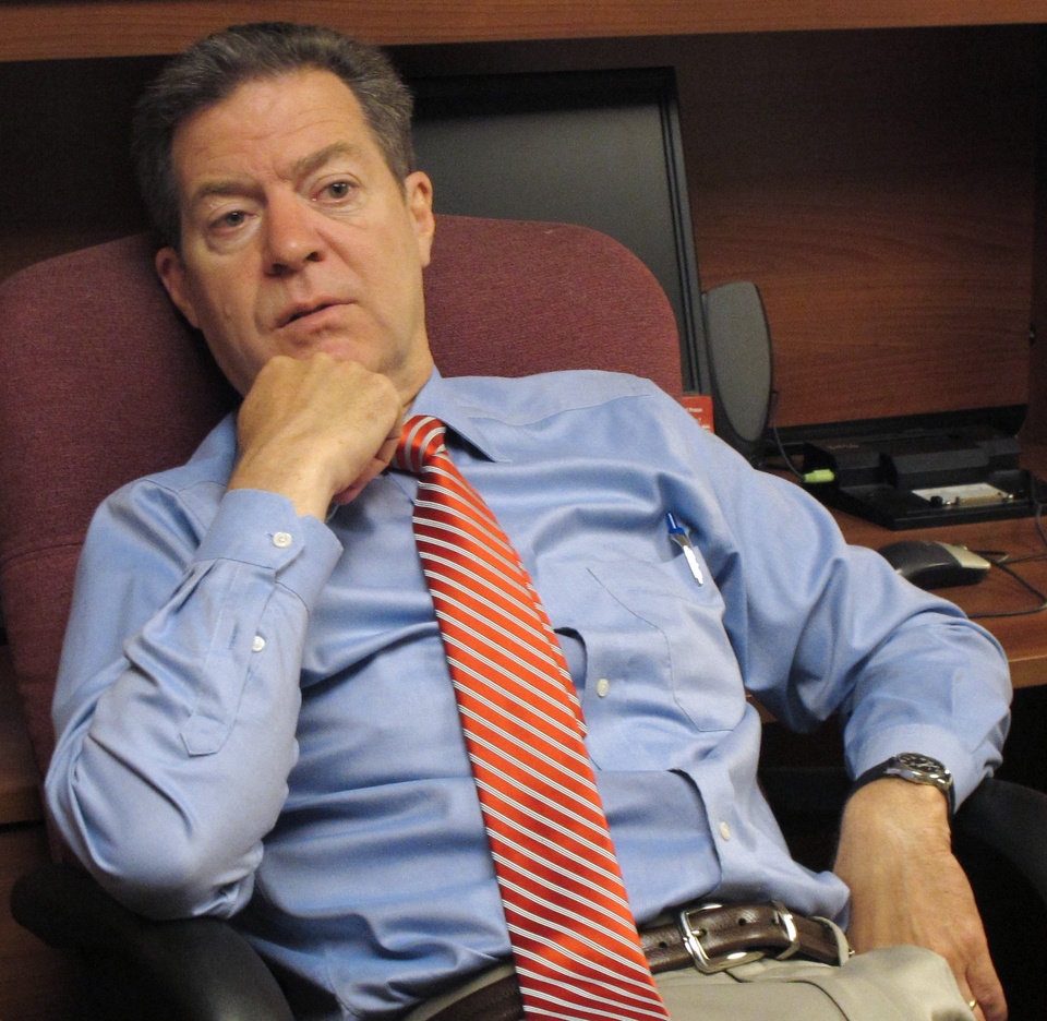 Photo - Kansas Gov. Sam Brownback ponders a question from  reporters during an impromptu visit to The Associated Press office at the Statehouse, Wednesday, July 23, 2014, in Topeka, Kan. Brownback called on wind-energy advocates and opponents of a renewable-energy rule to compromise on the policy's future. (AP Photo/Credit withheld)