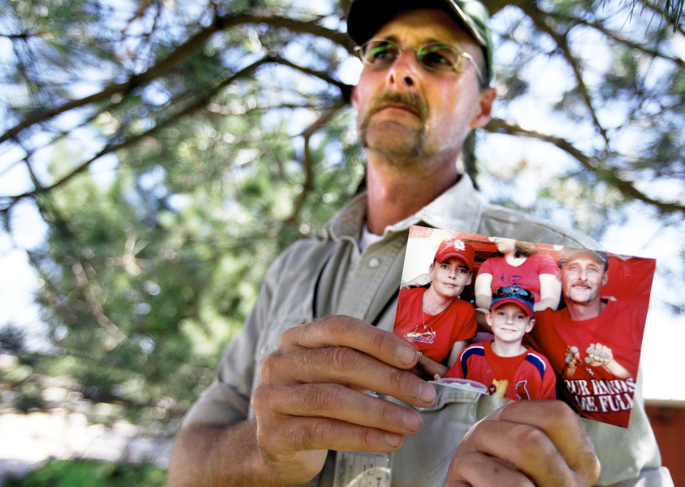 Photo - Kirk Smalley holds a picture of himself; his 11-year-old stepson, Ty Field; and wife, Laura. The three were attending a St. Louis Cardinals game. PHOTO BY MIRANDA GRUBBS, THE OKLAHOMAN
