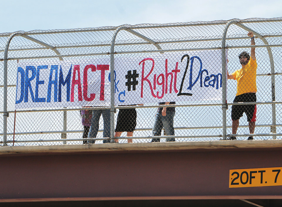 Photo - Amir Darvishzadeh holds his hand up in a fist to show solidarity while protesting Thursday on the walking bridge over Interstate 44 near Woodson Park in Oklahoma City. Photo by David McDaniel, The Oklahoman