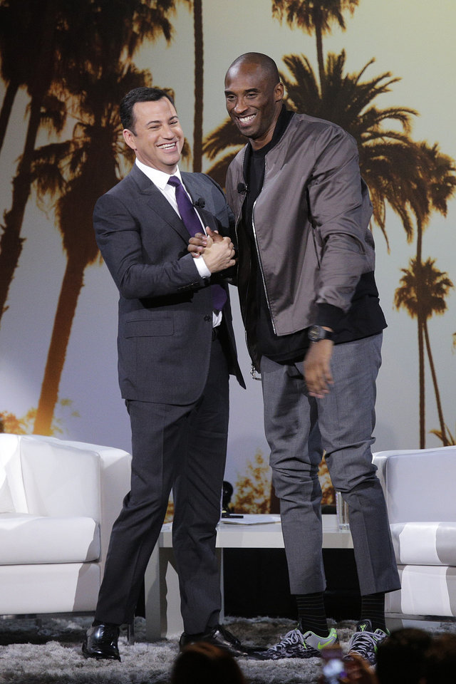 Photo - Los Angeles Lakers' Kobe Bryant, right, and talk show host Jimmy Kimmel shake hands after a one-on-one conversation at Nokia Theatre on Thursday, Aug. 15, 2013, in Los Angeles. The event was held to raise money toward eliminating homelessness in the Los Angeles area. (AP Photo/Jae C. Hong)