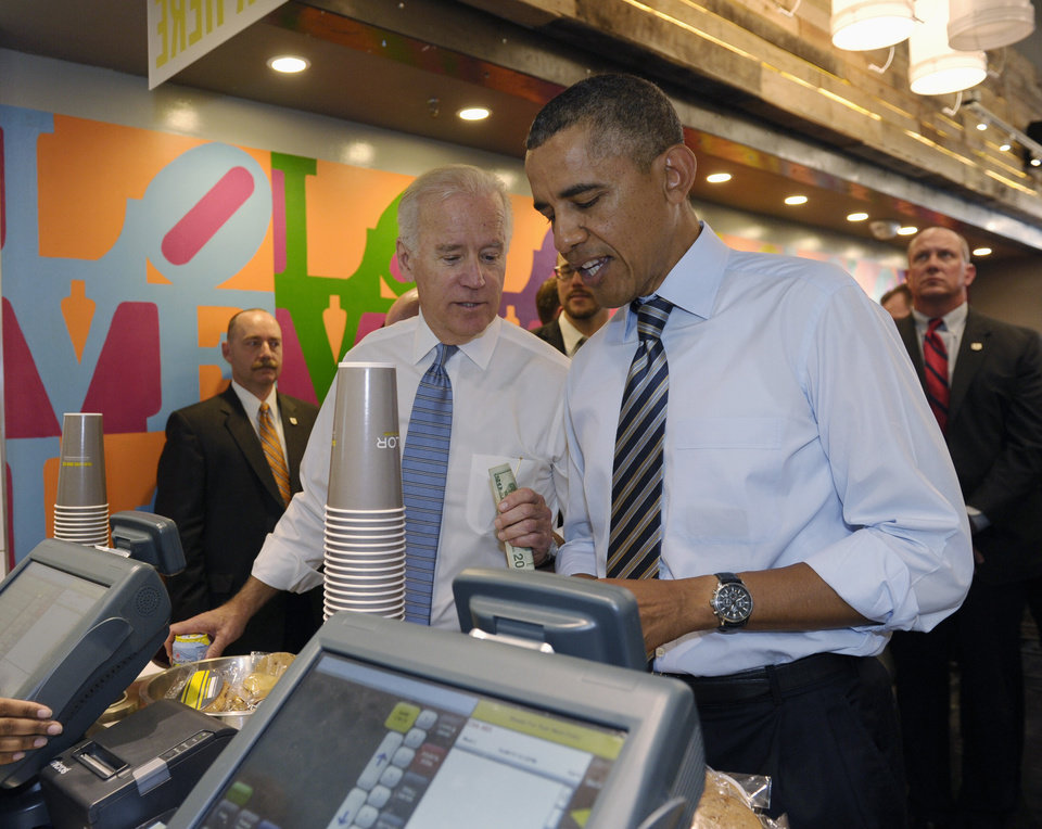 Photo - President Barack Obama and Vice President Joe Biden order lunch at Taylor Gourmet sandwich shop near the White House in Washington, Friday, Oct. 4, 2013. The president and vice president stepped out of the White House on a surprise and rare off-campus stroll to grab lunch at a neighborhood eatery.  (AP Photo/Susan Walsh)