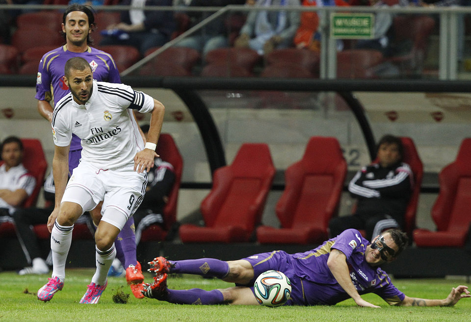 Photo - Real Madrid's Karim Benzema from France, left, and Fiorentina's  Gonzalo Rodriguez challenge for the ball during their friendly soccer match in Warsaw, Poland, Saturday, Aug. 16, 2014.(AP Photo/Czarek Sokolowski)