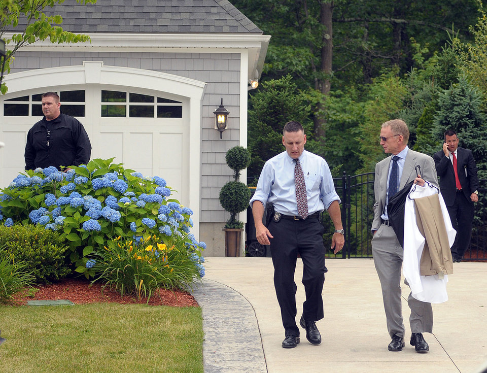 Photo - An unidentified attorney of former New England Patriots football player Aaron Hernandez, right, leaves Hernandez's home after securing some dress clothes from the house as police investigators work outside the home Thursday, June 27, 2013, in North Attleboro, Mass.  A judge on Thursday denied bail for the former NFL player, who is charged with first-degree murder in the shooting death of a friend. (AP Photo/The Attleboro Sun Chronicle, Mark Stockwell)  MAGS OUT. MANDATORY CREDIT, PROVIDENCE JOURNAL OUT