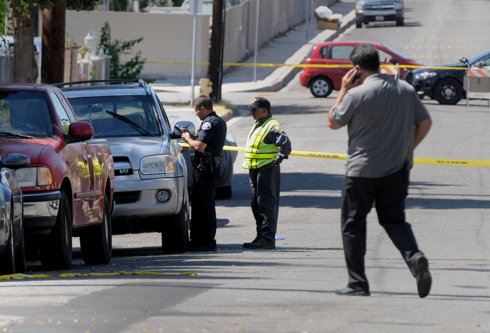 """Photo - Los Angeles Police Department officers investigate the scene of a shooting Sunday, Aug. 24, 2014, where one person was killed near the 14400 block of Polk Street in Sylmar, Calif.  Describing what they called """"a major public threat,"""" Los Angeles police said they are seeking clues to three separate shootings in the Northeast San Fernando Valley that left three people dead and four others injured early Sunday morning and appear to be connected. A suspect in the shootings was taken into custody by SWAT officers Sunday night after holing up inside a house in the Sylmar neighborhood for about an hour, Capt. William Hayes said.  (AP Photo/Los Angeles Daily News, Dean Musgrove)"""