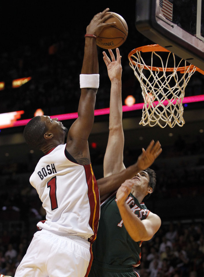Photo -   Miami Heat's Chris Bosh (1) goes to the basket as Milwaukee Bucks' Ersan Ilyasova (7), of Turkey, defends in the first half of an NBA basketball game, Wednesday, Nov. 21, 2012, in Miami. (AP Photo/Alan Diaz)