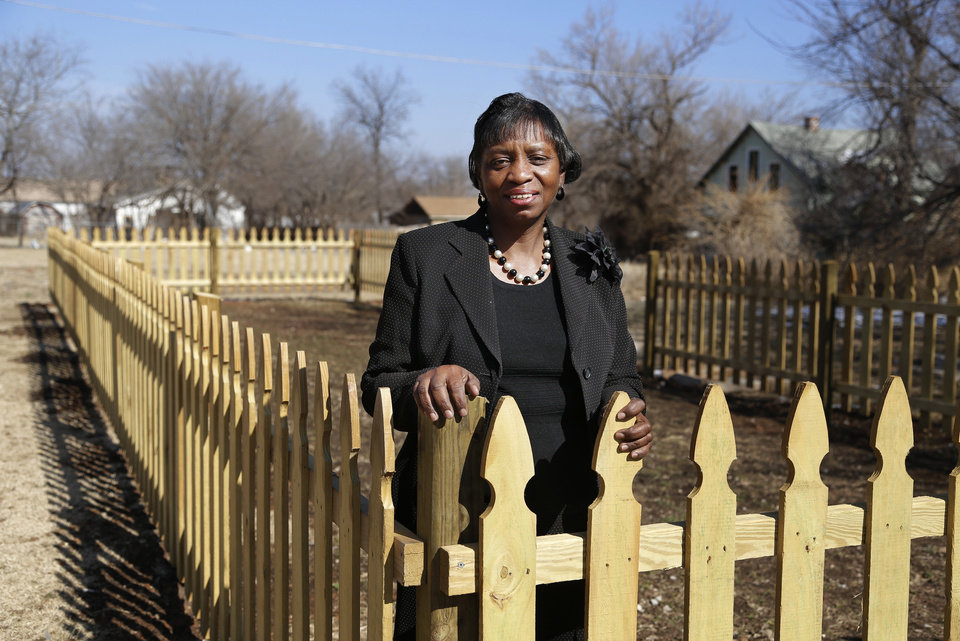 Photo - Marilyn Long stands inside the fence Eagle Scouts built to protect the community garden behind the Northeast Resource Center Wednesday. Photo by Doug Hoke, The Oklahoman  DOUG HOKE - THE OKLAHOMAN